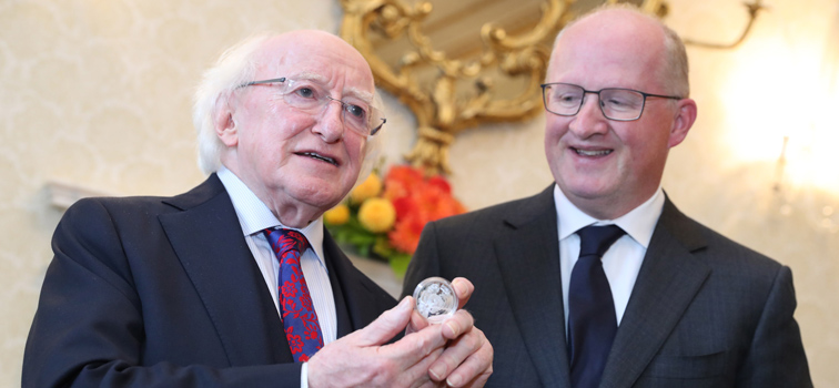 Governor presenting commemorative coin to President Higgins